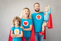 Οικογένεια των superheroes που παίζουν στο σπίτι στοκ φωτογραφία
