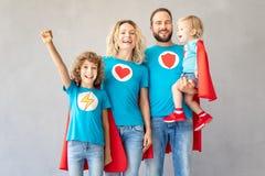 Οικογένεια των superheroes που παίζουν στο σπίτι στοκ εικόνα με δικαίωμα ελεύθερης χρήσης