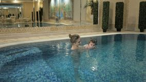οικογένεια υγιής Κοριτσάκι διδασκαλίας μητέρων που κολυμπά στη λίμνη απόθεμα βίντεο