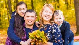 Οικογένεια, φύση, φθινόπωρο και έννοια ανθρώπων - πορτρέτο της ευτυχών μητέρας, του πατέρα, του γιου και της κόρης το φθινόπωρο Στοκ Εικόνες