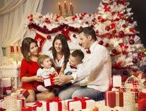 Οικογένεια Χριστουγέννων που ανοίγει το παρόν κιβώτιο δώρων, εορτασμός Χριστουγέννων στοκ εικόνες με δικαίωμα ελεύθερης χρήσης