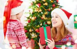 οικογένεια Χριστουγένν&o η μητέρα και το παιδί δίνουν τα δώρα Στοκ Φωτογραφίες