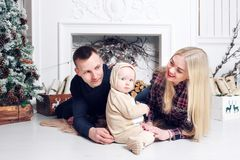 οικογένεια Χριστουγένν&o Οι γονείς και το μωρό που βρίσκονται στο πάτωμα και το χαμόγελο Στοκ Εικόνες