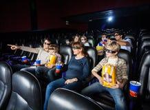 Οικογένειες που έχουν τα πρόχειρα φαγητά στην τρισδιάστατη κινηματογραφική αίθουσα Στοκ Εικόνες
