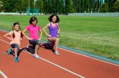 Οικογενειακά ικανότητα, μητέρα και παιδιά που εκπαιδεύουν στο στάδιο, αθλητισμός με τα παιδιά Στοκ Εικόνες