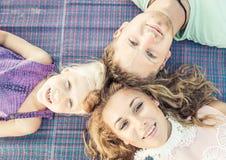 3 οικογενειακά κορίτσια καναπέδων φωτογραφικών μηχανών που φαίνονται πορτοκαλί πορτρέτο μητέρων σχετικά με το κάθισμά τους εκεί στοκ φωτογραφίες
