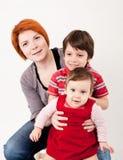 3 οικογενειακά κορίτσια καναπέδων φωτογραφικών μηχανών που φαίνονται πορτοκαλί πορτρέτο μητέρων σχετικά με το κάθισμά τους εκεί στοκ εικόνα