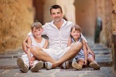 3 οικογενειακά κορίτσια καναπέδων φωτογραφικών μηχανών που φαίνονται πορτοκαλί πορτρέτο μητέρων σχετικά με το κάθισμά τους εκεί Στοκ Φωτογραφία