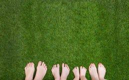 Οικογενειακά πόδια που στέκονται μαζί στην πράσινη χλόη Στοκ Φωτογραφία