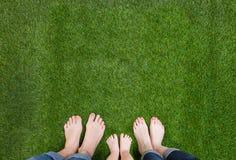 Οικογενειακά πόδια που στέκονται μαζί στην πράσινη χλόη Στοκ Εικόνα