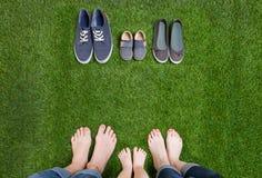 Οικογενειακά πόδια στα τζιν και παπούτσια που στέκονται στη χλόη Στοκ εικόνες με δικαίωμα ελεύθερης χρήσης