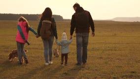 Οικογενειακά ταξίδια με το σκυλί στην πεδιάδα ομαδική εργασία μιας στενής οικογένειας μητέρα, λίγο παιδί και κόρες και κατοικίδια απόθεμα βίντεο
