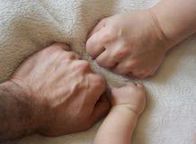 Οικογενειακά χέρια και μωρό νέα - γεννημένος βραχίονας Στοκ Εικόνες