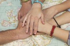 Οικογενειακά χέρια μαζί πέρα από έναν παγκόσμιο χάρτη απομονωμένο έννοια λευκό ομάδων Στοκ Εικόνες