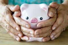 Οικογενειακά χέρια που καλύπτουν την καλή piggy τράπεζα Στοκ φωτογραφίες με δικαίωμα ελεύθερης χρήσης