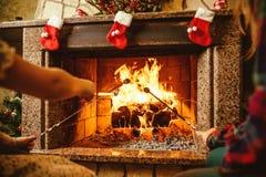 Οικογενειακά ψήνοντας marshmallows από την πυρκαγιά Άνετο σπίτι σαλέ με στοκ εικόνα