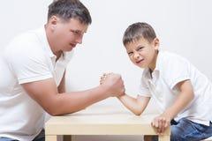 Οικογενειακές έννοιες Ο πατέρας έχει τα αστεία πρωταθλήματα Armwrestling Στοκ φωτογραφία με δικαίωμα ελεύθερης χρήσης