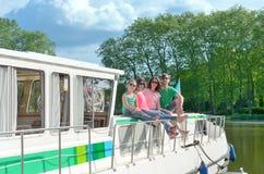 Οικογενειακές διακοπές, ταξίδι καλοκαιρινών διακοπών στη βάρκα φορτηγίδων στο κανάλι, ευτυχείς παιδιά και γονείς που έχουν τη δια Στοκ Εικόνες