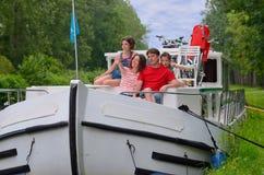 Οικογενειακές διακοπές, ταξίδι στη βάρκα φορτηγίδων στο κανάλι, γονείς με τα παιδιά που έχουν τη διασκέδαση στην κρουαζιέρα ποταμ Στοκ Φωτογραφίες