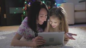 Οικογενειακές μητέρα και κόρη που επιλέγουν τα δώρα στην ψηφιακή ταμπλέτα ενώ ψέμα στο πάτωμα στενός κόκκινος χρόνος Χριστουγέννω φιλμ μικρού μήκους