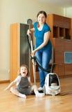 Οικογενειακές μικροδουλειές με την ηλεκτρική σκούπα Στοκ Φωτογραφία