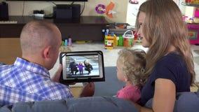 Οικογενειακές φωτογραφίες προσοχής κοριτσιών γυναικών και μικρών παιδιών ανδρών στο PC ταμπλετών στο σπίτι απόθεμα βίντεο