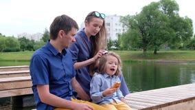 Οικογενειακή έννοια: συνεδρίαση μητέρων, πατέρων και μικρών παιδιών από τον ποταμό Μητέρα που κτενίζει την τρίχα του παιδιού απόθεμα βίντεο