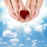 Οικογενειακή έννοια - χέρια των γονέων που κρατούν τα χέρια παιδιών με την καρδιά Στοκ Φωτογραφίες