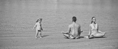 Οικογενειακή γιόγκα μητέρα, πατέρας και παιδί που κάνουν τις ασκήσεις γιόγκας στην παραλία στοκ εικόνα