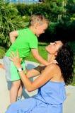 οικογενειακή ευτυχής & Μητέρα με το παιδικό παιχνίδι, τα φιλιά και τα αγκαλιάσματα Στοκ Φωτογραφίες