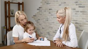 Οικογενειακή κλινική Όμορφη μητέρα και το θηλυκό παιδί της στο γραφείο γιατρών Σχέδιο παιδιών ενώ ομιλία μητέρων και γιατρών γενι απόθεμα βίντεο