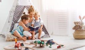 Οικογενειακή μητέρα που διαβάζει στο βιβλίο παιδιών στη σκηνή στο σπίτι στοκ φωτογραφία με δικαίωμα ελεύθερης χρήσης