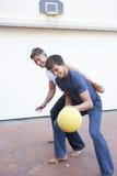 Οικογενειακή παίζοντας καλαθοσφαίριση πατέρων και εφήβων γιος έξω από το γκαράζ Στοκ εικόνες με δικαίωμα ελεύθερης χρήσης