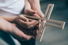 Οικογενειακή προσευχή με τον ξύλινο σταυρό στοκ φωτογραφίες