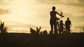 Οικογενειακή σκιαγραφία ποδηλατών, γονείς με δύο παιδιά στα ποδήλατα στο ηλιοβασίλεμα Έννοια της φιλικής οικογένειας απόθεμα βίντεο