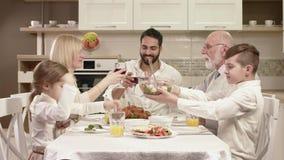 Οικογενειακή συνεδρίαση γύρω από έναν πίνακα, τρώγοντας, επικοινωνώντας και έχοντας τη διασκέδαση κατά τη διάρκεια του οικογενεια φιλμ μικρού μήκους