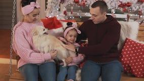Οικογενειακή συνεδρίαση στην ταλάντευση κοντά στο χριστουγεννιάτικο δέντρο στο μέρος οικογενειακά καρύδια έννοιας σύνθεσης μπουλο φιλμ μικρού μήκους