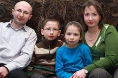 Οικογενειακή συνεδρίαση στον καναπέ και χαμόγελο στοκ φωτογραφία με δικαίωμα ελεύθερης χρήσης