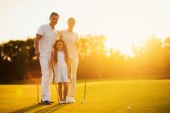 Οικογενειακή τοποθέτηση σε ένα γήπεδο του γκολφ που κρατά ένα γκολφ κλαμπ σε ένα υπόβαθρο ηλιοβασιλέματος Στοκ Εικόνα