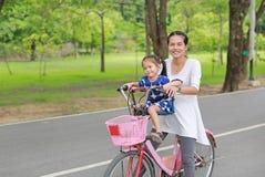 Οικογενειακή υπαίθρια δραστηριότητα Ασιατική μητέρα και το κορίτσι παιδιών της σε ένα ποδήλατο στο πάρκο το πρωί στοκ εικόνα