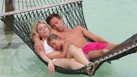 Οικογενειακή χαλάρωση στην αιώρα παραλιών απόθεμα βίντεο