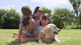 Οικογενειακή χαλάρωση στον κήπο με το σκυλί της Pet απόθεμα βίντεο
