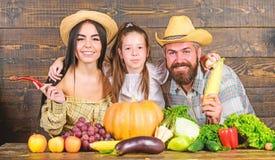 Οικογενειακοί αγρότες με το ξύλινο υπόβαθρο συγκομιδών Αγρότες οικογενειακού αγροτικοί ύφους στην αγορά με τα φρούτα και την πρασ στοκ φωτογραφία