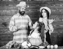 Οικογενειακοί αγρότες με το ξύλινο υπόβαθρο συγκομιδών Οι γονείς και η κόρη γιορτάζουν το φεστιβάλ συγκομιδών φθινοπώρου Οικογένε στοκ εικόνα με δικαίωμα ελεύθερης χρήσης