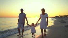 Οικογενειακοί περίπατοι στην παραλία Περίπατος γονέων με τη μικρή κόρη τους κατά μήκος της ακτής Κρατούν τα χέρια Είναι ευτυχείς φιλμ μικρού μήκους