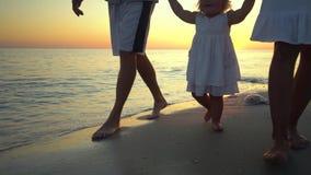 Οικογενειακοί περίπατοι στην παραλία Περίπατος γονέων με τη μικρή κόρη τους κατά μήκος της ακτής Κρατούν τα χέρια Είναι ευτυχείς απόθεμα βίντεο