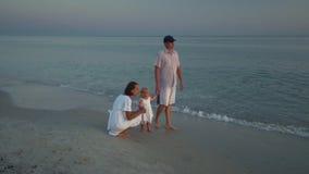 Οικογενειακοί περίπατοι στην παραλία Περίπατος γονέων με τη μικρή κόρη τους κατά μήκος της ακτής Γονείς που σκύβονται εκτός από τ απόθεμα βίντεο