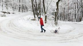 οικογενειακός περίπατ&omic Πατέρας και κόρη με το έλκηθρο στον όρμο χειμερινού χιονιού Στοκ εικόνα με δικαίωμα ελεύθερης χρήσης