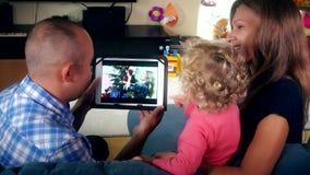 Οικογενειακός τηλεοπτικός κινηματογράφος ρολογιών καλών οικογενειακών παιδιών πατέρων και μητέρων στην ταμπλέτα απόθεμα βίντεο