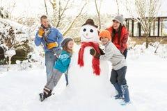 Οικογενειακός χτίζοντας χιονάνθρωπος στον κήπο στοκ φωτογραφία
